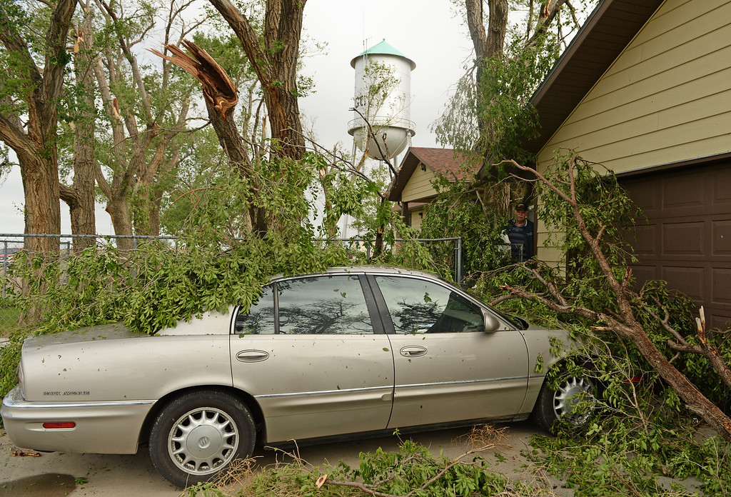 . Gary Ensign checks out the damage to his car, in Hugo, after a lager storm moved through town over night, June 5, 2014.  (Photo by RJ Sangosti/The Denver Post)