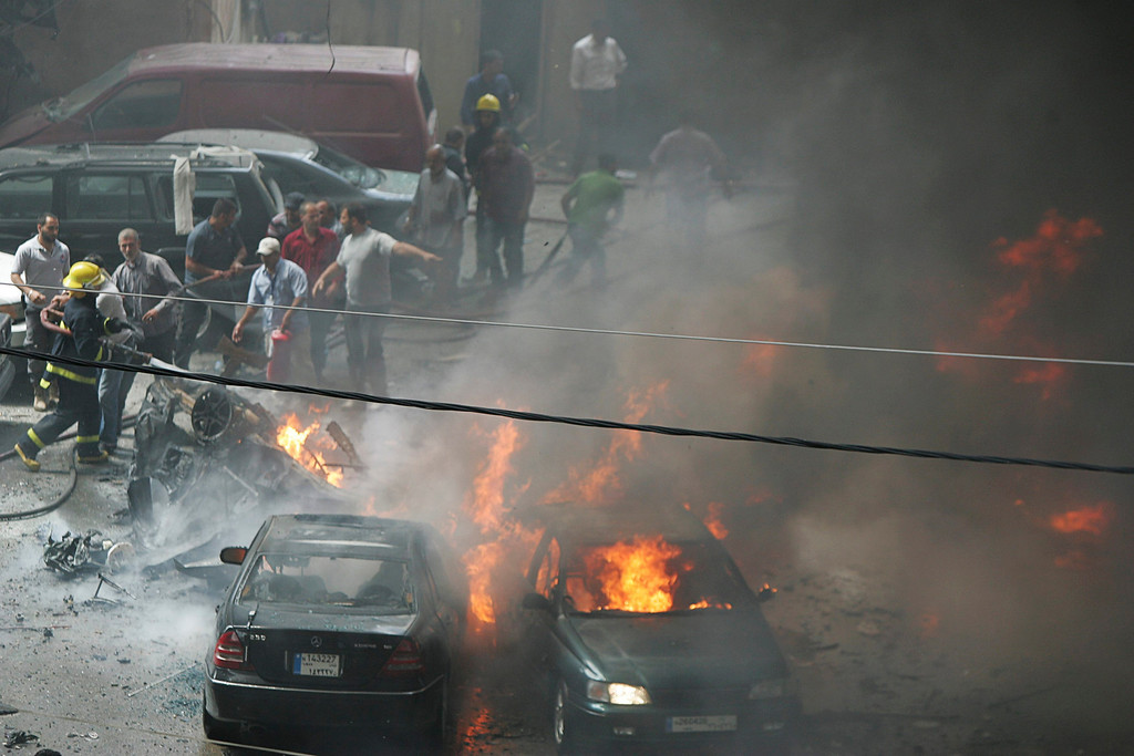 . Civil Defense members extinguish fire from burning cars as people gather at the site of an explosion in Beirut\'s southern suburbs July 9, 2013.  REUTERS/Issam Kobeisi