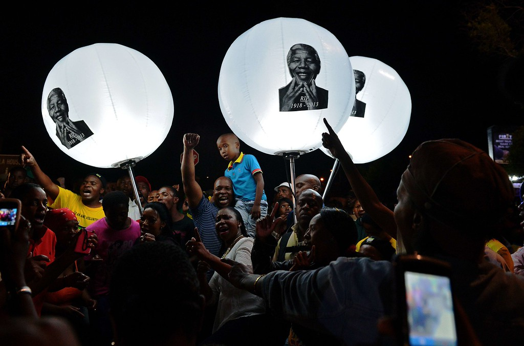 . People hold up balloon lamps bearing the image of late former South African president Nelson Mandela during a commemorative ceremony outside the late leader\'s former home in the Orlando West district of Johannesburg on December 7, 2013.  AFP PHOTO / Carl de SOUZA/AFP/Getty Images