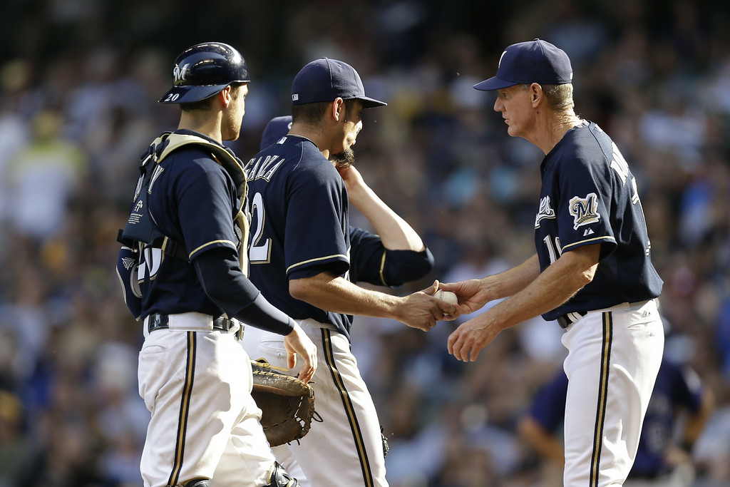 . MILWAUKEE, WI - JUNE 28: Matt Garza #22 of the Milwaukee Brewers hands the ball off to Manager Ron Roenicke #13 and heads to the dugout during the bottom of the sixth inning against the Colorado Rockies at Miller Park on June 28, 2014 in Milwaukee, Wisconsin. (Photo by Mike McGinnis/Getty Images)