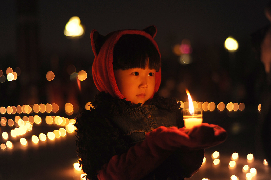 . This photo taken on April 21, 2013 shows a little girl holding a candle in her hands while people gather to pray for disaster-hit Yaan in Daqing, northeast China\'s Heilongjiang province. STR/AFP/Getty Images
