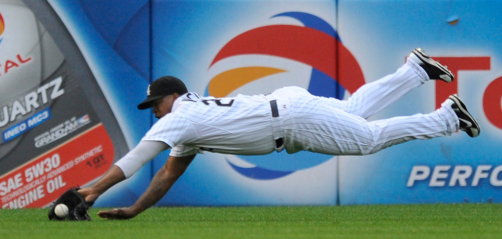 . Chicago White Sox left fielder Dayan Viciedo misses a single hit by New York Yankees\' Robinson Cano during the first inning of a baseball game in Chicago, Monday, Aug. 5, 2013. (AP Photo/Paul Beaty)