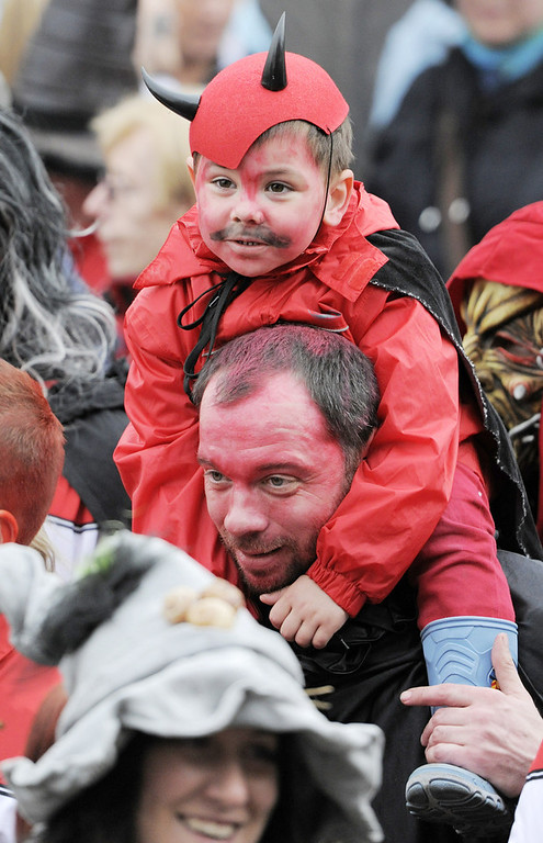 . Ronny Wechenberger and his son Rion, costumed as a little devil, take part at a procession in Schierke, central Germany, Tuesday, April 30, 2013. Hundreds of costumed devils and witches meet to celebrate Walpurgis Night, a traditional religious holiday of pre-Christian origins. The event is named after St. Walburga, an English nun who helped convert the Germans to Christianity in the 8th century. (AP Photo/Jens Meyer)