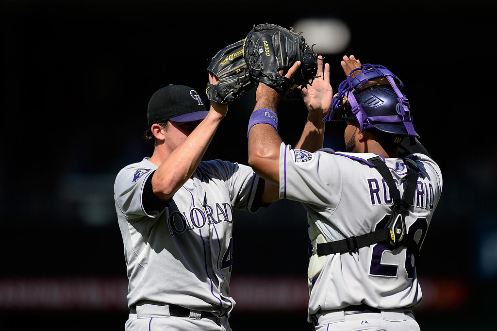 . Rex Brothers #49 of the Colorado Rockies celebrates with Wilin Rosario #20 after the Rockies defeated the Washington Nationals 7-6 during a game at Nationals Park on June 23, 2013 in Washington, DC.  (Photo by Patrick McDermott/Getty Images)