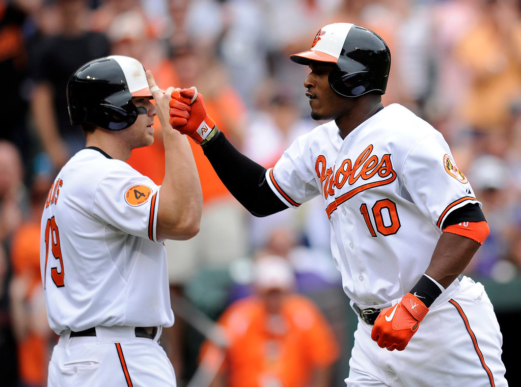 . Baltimore Orioles\' Adam Jones (10) celebrates his two-run home run with teammate Chris Davis, left, against the Colorado Rockies during the third inning of a baseball game on Sunday, Aug. 18, 2013, in Baltimore. (AP Photo/Nick Wass)