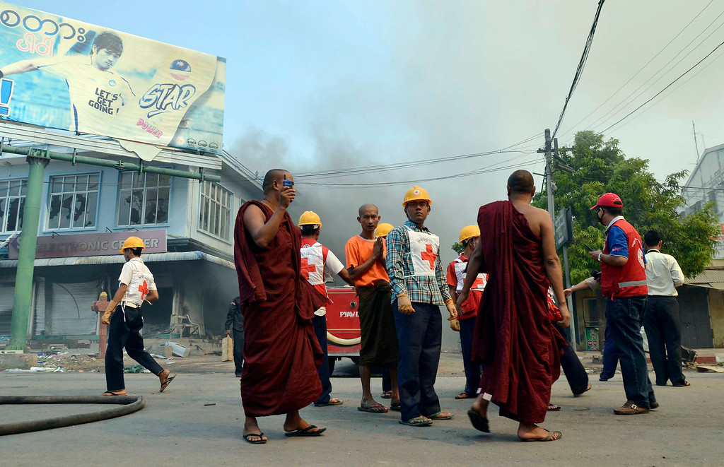 . Buddhist monks and members of Red Cross team gather as Myanmar fire fighters put out fires in burning building following ethnic unrest between Buddhists and Muslims in Meikhtila, Mandalay division, about 550 kilometers (340 miles) north of Yangon, Myanmar, Friday, March 22, 2013. (AP Photo/Khin Maung Win)