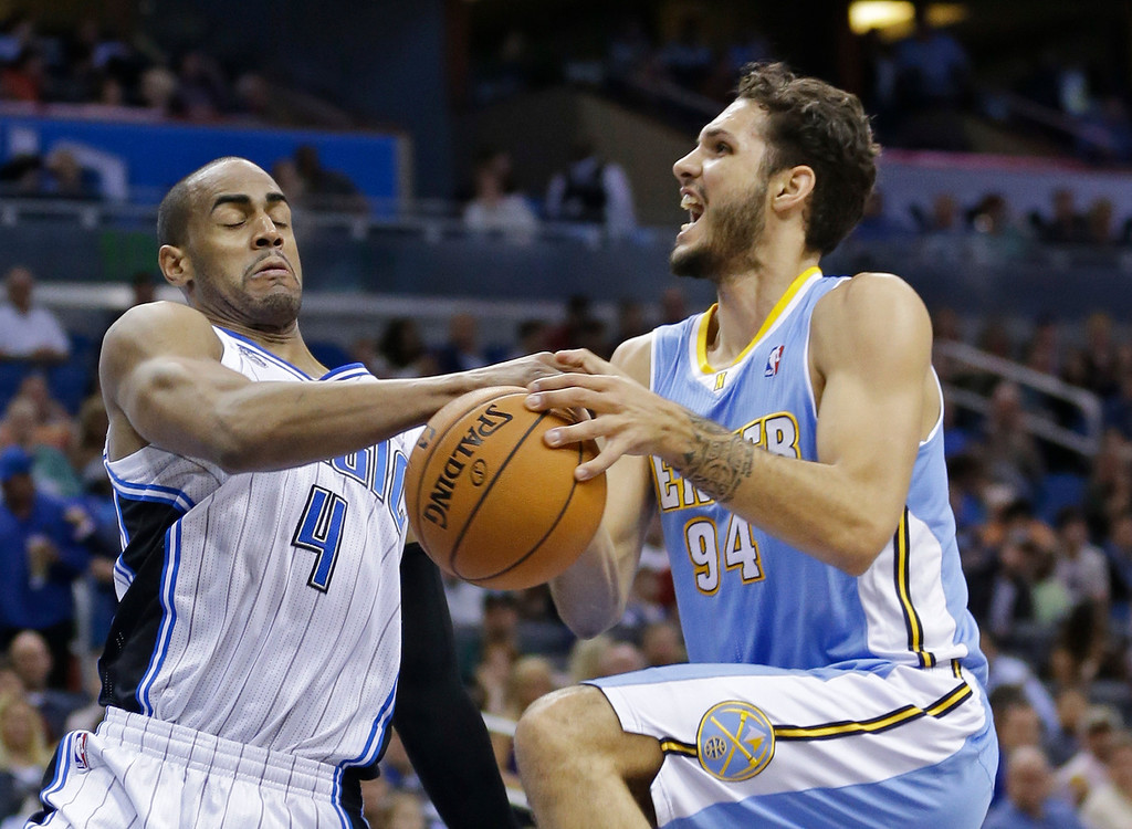 . Orlando Magic\'s Arron Afflalo (4) knocks the ball out of the hands of Denver Nuggets\'s Evan Fournier (94) as he goes up for a shot during the first half of an NBA basketball game in Orlando, Fla., Wednesday, March 12, 2014. (AP Photo/John Raoux)