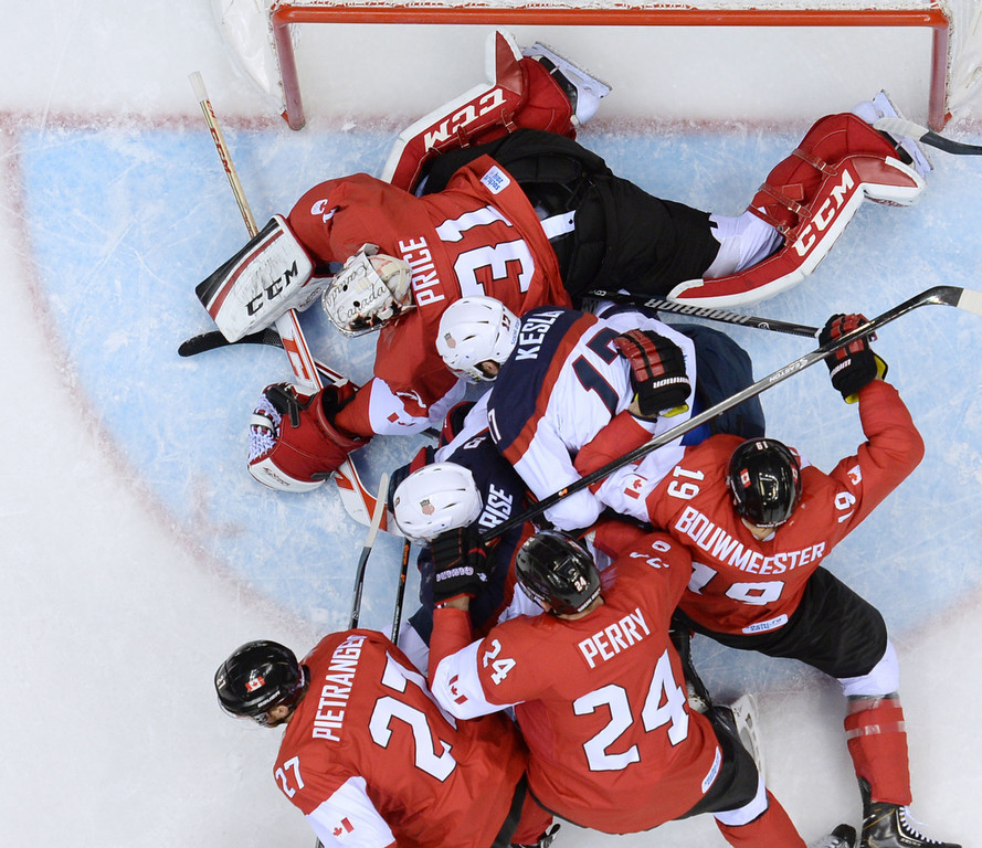 . US Ryan Kesler and US Zach Parise (C) fight for the puck with Canadian players during the Men\'s Ice Hockey Semifinals USA vs Canada at the Bolshoy Ice Dome during the Sochi Winter Olympics on February 21, 2014.   ALEXANDER NEMENOV/AFP/Getty Images