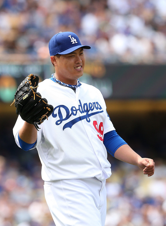 . Hyun-Jin Ryu #99 of  the Los Angeles Dodgers reacts after making a fielding error in thefifth inning of the game against the Colorado Rockies at Dodger Stadium on April 27, 2014 in Los Angeles, California.  (Photo by Stephen Dunn/Getty Images)