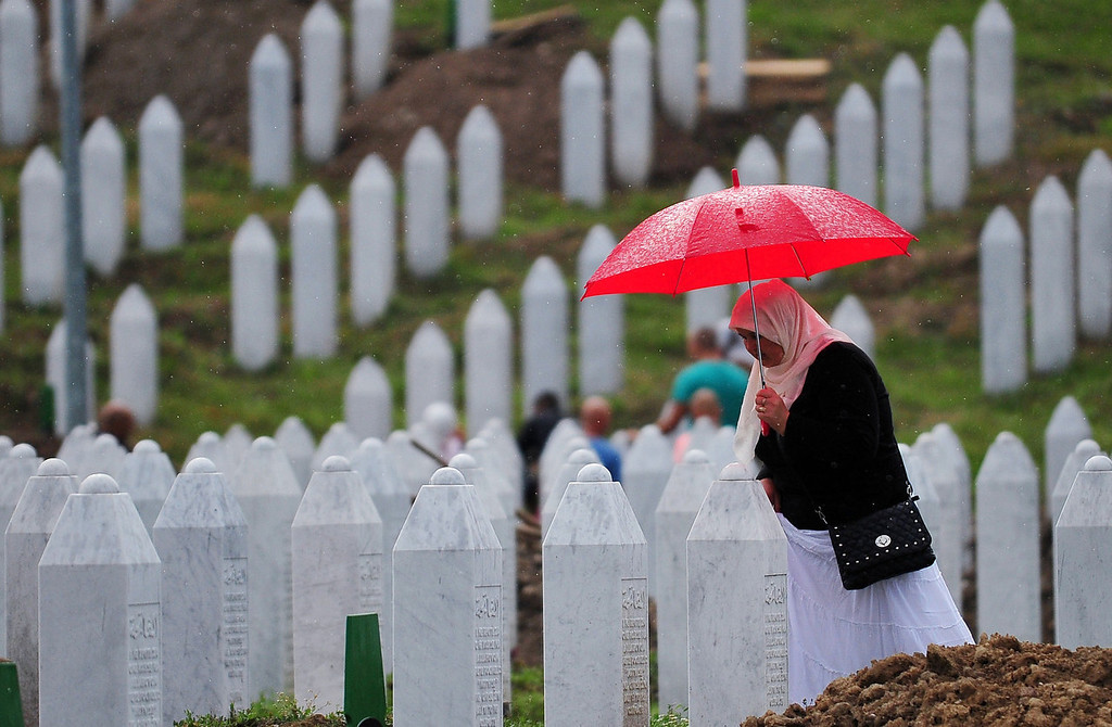 . A Bosnian Muslim woman, survivor of the Srebrenica 1995 massacre, searches for a burial plot intended for her relative, at the memorial cemetery in the village of Potocarion near the Eastern-Bosnian town of Srebrenica, on July 10, 2013. Potocari Memorial cemetery is undergoing preparations for another mass burial on July 11, when 409 newly identified bodies will be put to final rest. Bodies are identified as those belonging to Bosnian Muslim victims of the offensive undertaken by Bosnian Serbs in July 1995 with aim to occupy the earlier declared UN safe heaven area of Srebrenica and the surrounding villages. During the offensive more than 8000 Bosnian non-Serbs went missing to be found buried in mass graves, years after the war ended.  ELVIS BARUKCIC/AFP/Getty Images