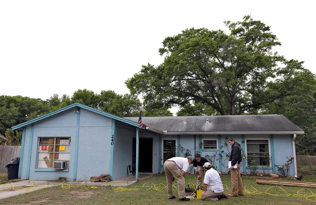 . Engineers work in front of a home where sinkhole opened up underneath a bedroom and swallowed a man Friday, March 1, 2013, in Seffner, Fla.  (AP Photo/Chris O\'Meara)