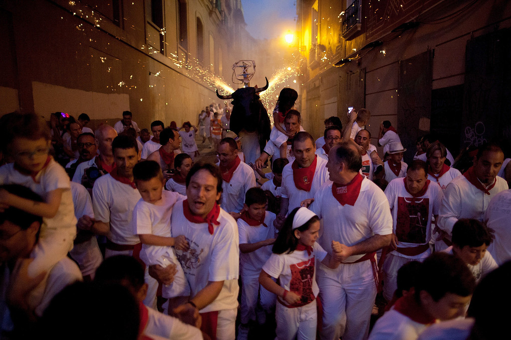 . PAMPLONA, SPAIN - JULY 09:  A Toro del Fuego (flaming bull) is run through the streets of Pamplona on the fourth day of the San Fermin Running Of The Bulls festival, on July 9, 2013 in Pamplona, Spain. The annual Fiesta de San Fermin, made famous by the 1926 novel of US writer Ernest Hemmingway \'The Sun Also Rises\', involves the running of the bulls through the historic heart of Pamplona, this year for nine days from July 6-14.  (Photo by Pablo Blazquez Dominguez/Getty Images)