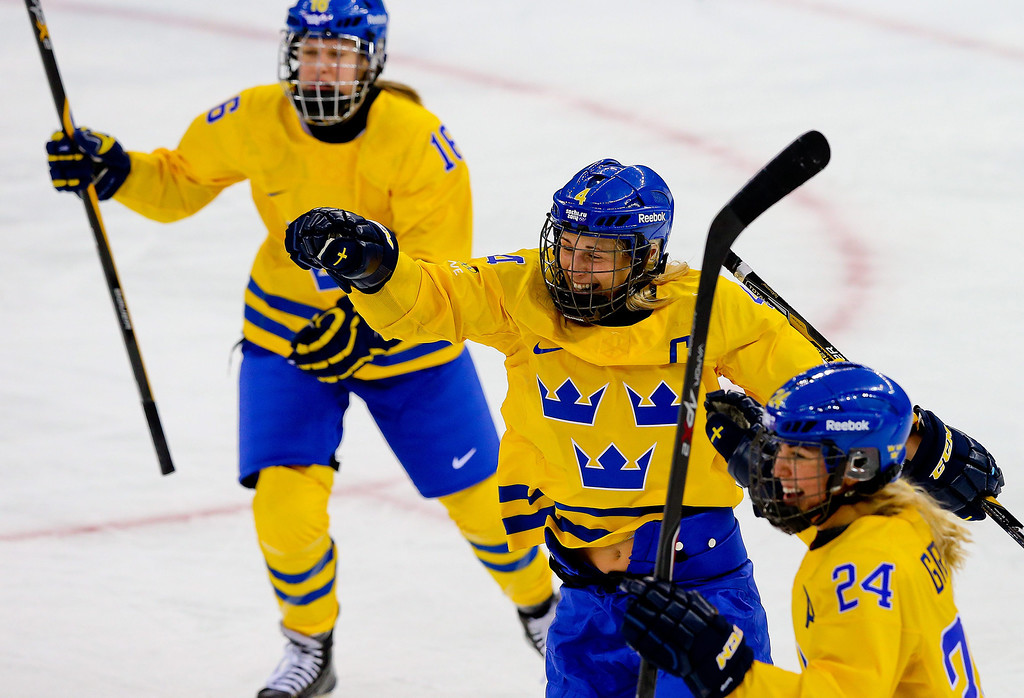 . Jenni Asserholt (C) of Sweden celebrates after scoring against Japan during the match between Sweden and Japan at the Shayba Arena in the Ice Hockey tournament at the Sochi 2014 Olympic Games, Sochi, Russia, 09 February 2014  EPA/SRDJAN SUKI