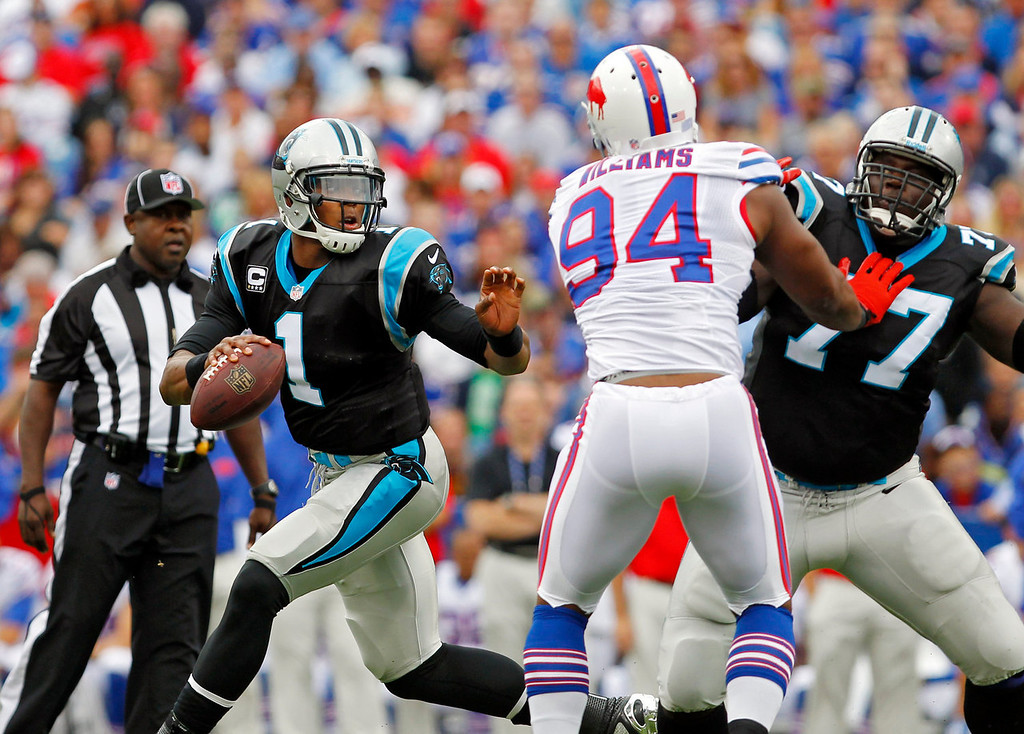 . Carolina Panthers quarterback Cam Newton (1) scrambles away from Buffalo Bills defensive end Mario Williams (94) as Byron Bell (77) blocks in the first quarter of an NFL football game Sunday, Sept. 15, 2013, in Orchard Park, N.Y. (AP Photo/Bill Wippert)