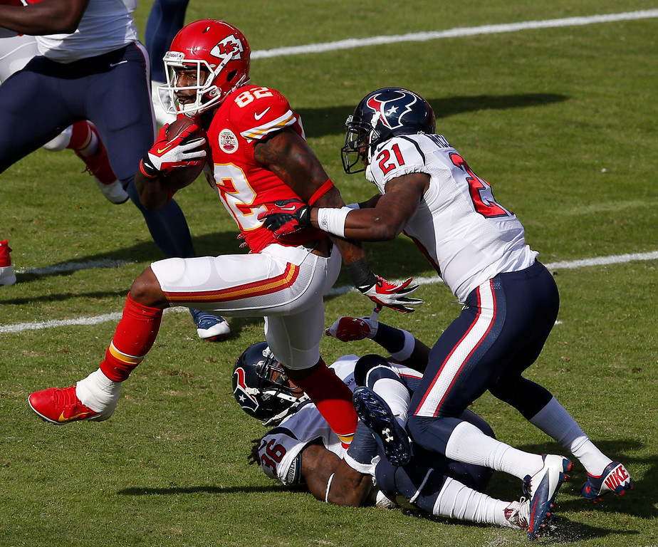 . Kansas City Chiefs wide receiver Dwayne Bowe (82) is tackled by Houston Texans strong safety D.J. Swearinger (36) and cornerback Brice McCain (21) during the first half of an NFL football game at Arrowhead Stadium in Kansas City, Mo., Sunday, Oct. 20, 2013. (AP Photo/Orlin Wagner)