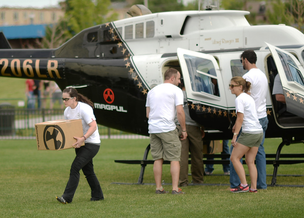 . GLENDALE, CO. - June 29: Volunteers move the box of 30-round gun magazines from the helicopter to a tent at a farewell to arms freedom festival by Free Colorado in Infinity Park. Glendale, Colorado. June 29, 2013. Magpul Industries attended the party and handed out 1500 of their 30-round gun magazines for free.  (Photo By Hyoung Chang/The Denver Post)