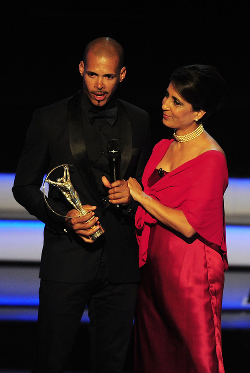 ". Athlete Felix Sanchez accepts his award for ""Laureus World Comebcak of the Year\""  from Laureus Academy Member Nawal El Moutawakel during the awards show for the 2013 Laureus World Sports Awards at the Theatro Municipal Do Rio de Janeiro on March 11, 2013 in Rio de Janeiro, Brazil.  (Photo by Jamie McDonald/Getty Images For Laureus)"