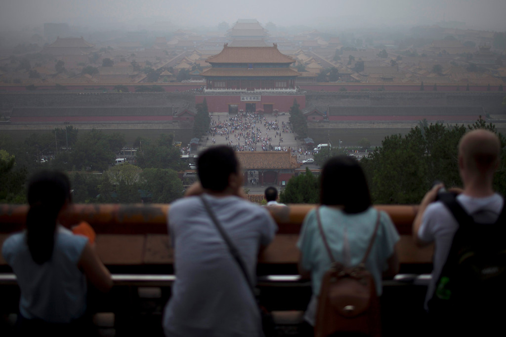 ". In this photo taken on June 29, 2013, tourists look at the Forbidden City from the top of Jinshan hill on a hazy day in Beijing, China. China\'s tourism industry has grown at a fast pace since the country began free market-style economic reforms three decades ago. However, it\'s latest tourism slogan ""Beautiful China\"" has been derided as particularly inept at a time when record-busting smog has drawn attention to the environmental and health costs of China\'s unfettered industrialization. Some point to unsophisticated marketing as an explanation.  (AP Photo/Alexander F. Yuan)"