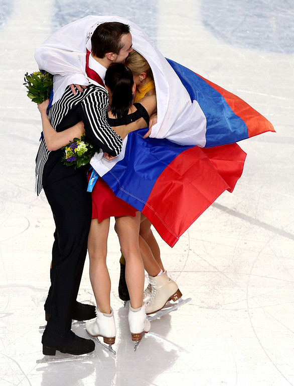. Silver medalists Ksenia Stolbova and Fedor Klimov of Russia, gold medalists Tatiana Volosozhar and Maxim Trankov of Russia celebrate during the flower ceremony for the Figure Skating Pairs event during day five of the 2014 Sochi Olympics at Iceberg Skating Palace on February 12, 2014 in Sochi, Russia.  (Photo by Clive Mason/Getty Images)