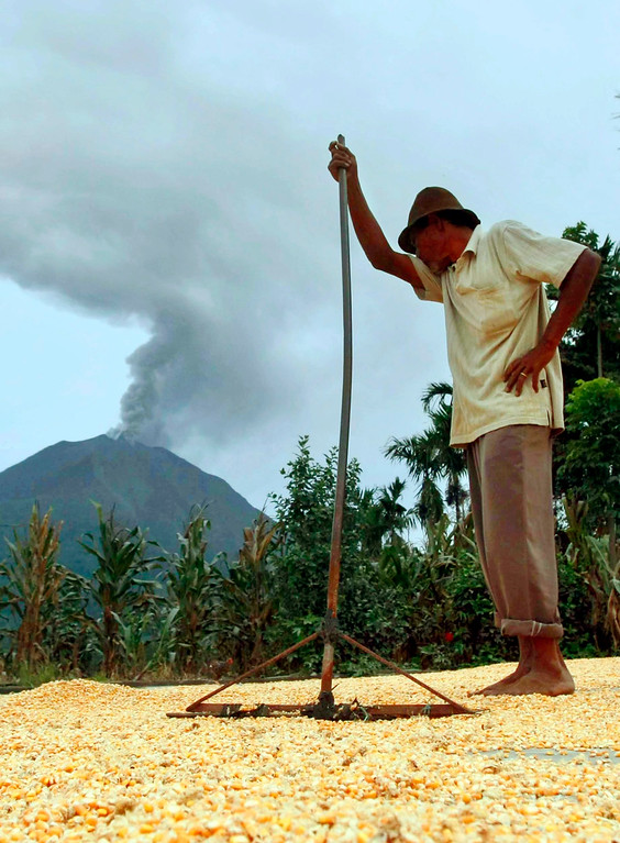 . An Indonesian villager dries corn as Mount Sinabung spews volcanic ash at  Guru Kinayan village, Karo, North Sumatra, Indonesia, 26 November 2013.   EPA/DEDI SAHPUTRA