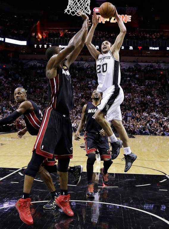 . San Antonio Spurs guard Manu Ginobili (20) goes in for a dunk over Miami Heat center Chris Bosh (1) during the first half in Game 5 of the NBA basketball finals on Sunday, June 15, 2014, in San Antonio. (AP Photo/David J. Phillip)