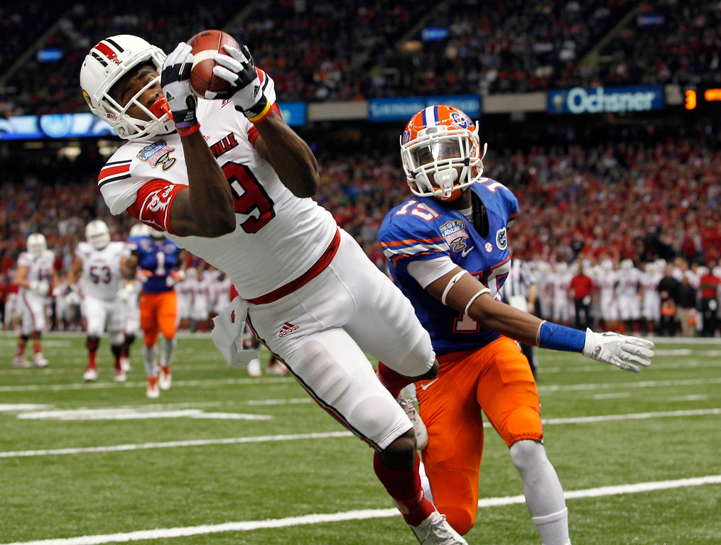 . Louisville Cardinals wide receiver DeVante Parker (L) catches a second quarter touchdown pass as Florida Gators defensive back Loucheiz Purifoy pursues during the 2013 Allstate Sugar Bowl NCAA football game in New Orleans, Louisiana January 2, 2013. REUTERS/Jonathan Bachman