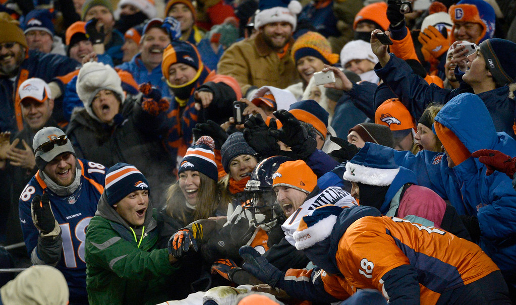. , DENVER, CO - DECEMBER 8: Denver Broncos running back Montee Ball (28) in the stands with fans after scoring a fourth quarter touchdown. The Denver Broncos vs. the Tennessee Titans at Sports Authority Field at Mile High in Denver on December 8, 2013. (Photo by Tim Rasmussen/The Denver Post)