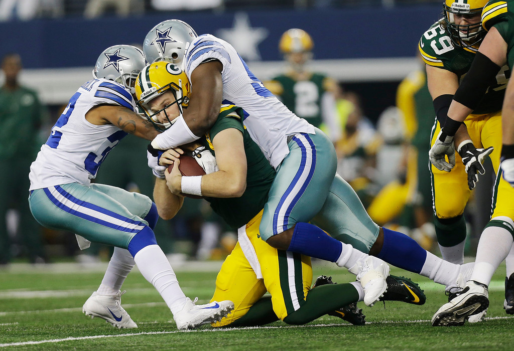 . Green Bay Packers quarterback Matt Flynn (10) is sacked by Dallas Cowboys cornerback Orlando Scandrick (32) and defensive end DeMarcus Ware (94) during the first half or an NFL football game, Sunday, Dec. 15, 2013, in Arlington, Texas. (AP Photo/Tim Sharp)