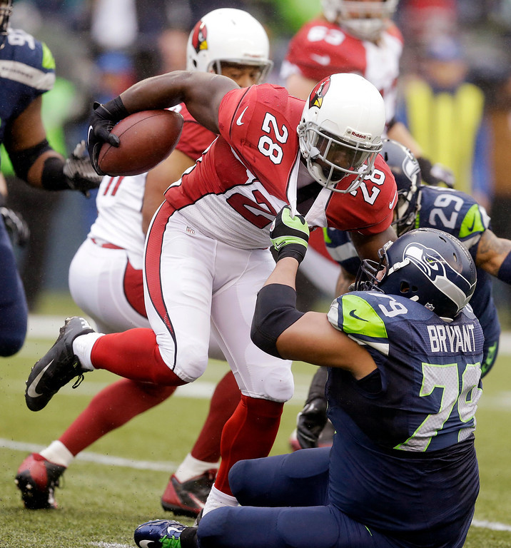 . Seattle Seahawks\' Red Bryant (79) pulls down Arizona Cardinals\' Rashard Mendenhall on a run in the first half of an NFL football game, Sunday, Dec. 22, 2013, in Seattle. (AP Photo/Elaine Thompson)