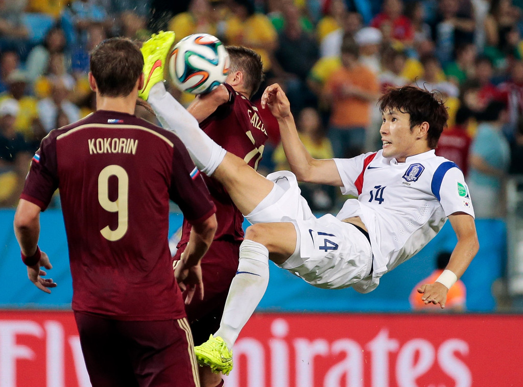 . South Korea\'s Hong Jeong-ho, right, scissor kicks the ball between Russia\'s Viktor Fayzulin and Alexander Kokorin (9) during the group H World Cup soccer match between Russia and South Korea at the Arena Pantanal in Cuiaba, Brazil, Tuesday, June 17, 2014.  (AP Photo/Ivan Sekretarev)