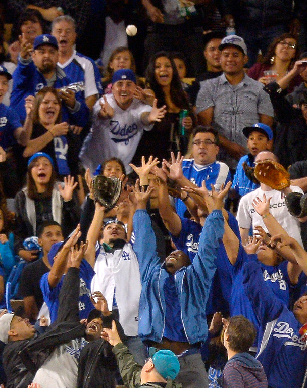 . Fans reach for a ball hit for a two-run home run by Los Angeles Dodgers\' A.J. Ellis during the fifth inning of their baseball game against the Colorado Rockies, Friday, Sept. 27, 2013, in Los Angeles.  (AP Photo/Mark J. Terrill)