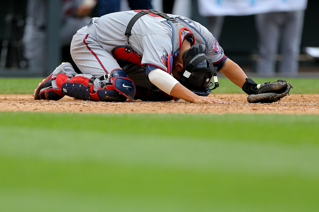 . Catcher Kurt Suzuki #8 of the Minnesota Twins lies on the ground in pain after a foul ball hit him during the fifth inning against the Colorado Rockies at Coors Field on July 13, 2014 in Denver, Colorado. The Twins defeated the Rockies 13-5. (Photo by Justin Edmonds/Getty Images)