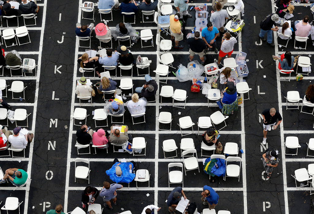 . Spectators mill about near the track at Pimlico Race Course in Baltimore, Saturday, May 18, 2013, before the Preakness Stakes horse race. (AP Photo/Patrick Semansky)