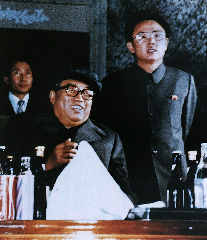 . Photo released by the Korea News Service dated October 1980 shows North Korean leader Kim Jong-Il (R) and father Kim Il-Sung (front), attending an evening party to celebrate the 6th Korean Worker\'s Party convention.  Kim Jong-Il was re-elected as head of the country\'s powerful National Defense Commission, Pyongyang Radio said 05 September, as CNN reported the title of president had been abolished in defense to Kim Il-Sung\'s father who died in 1994, leaving Kim Il-Sung as effective head of state.    (AFP/Getty Images)