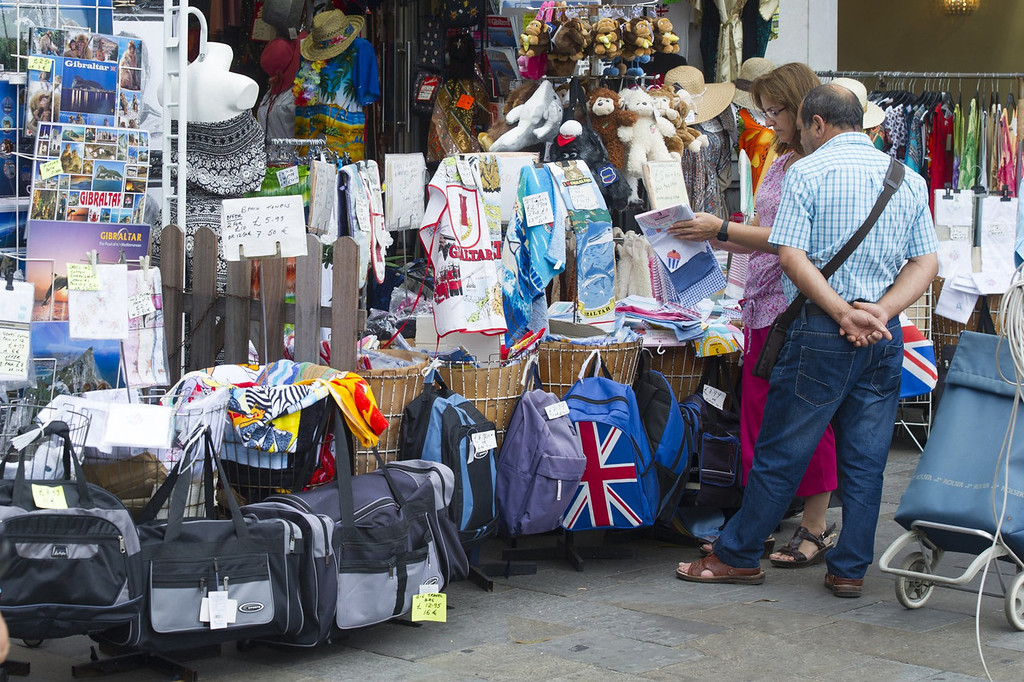 ". Tourists look at store goods on Casemates square in Gibraltar on August 13, 2013 as Spain today enforced tight border checks in a growing row with Britain over the tiny territory and its surrounding waters. On the ""Rock\"" itself, defiant residents declared themselves thoroughly British, surrounded by English pubs serving fish and chips, Royal Mail letter boxes, bright red telephone cabins and the occasional monkey.    MARCOS MORENO/AFP/Getty Images"