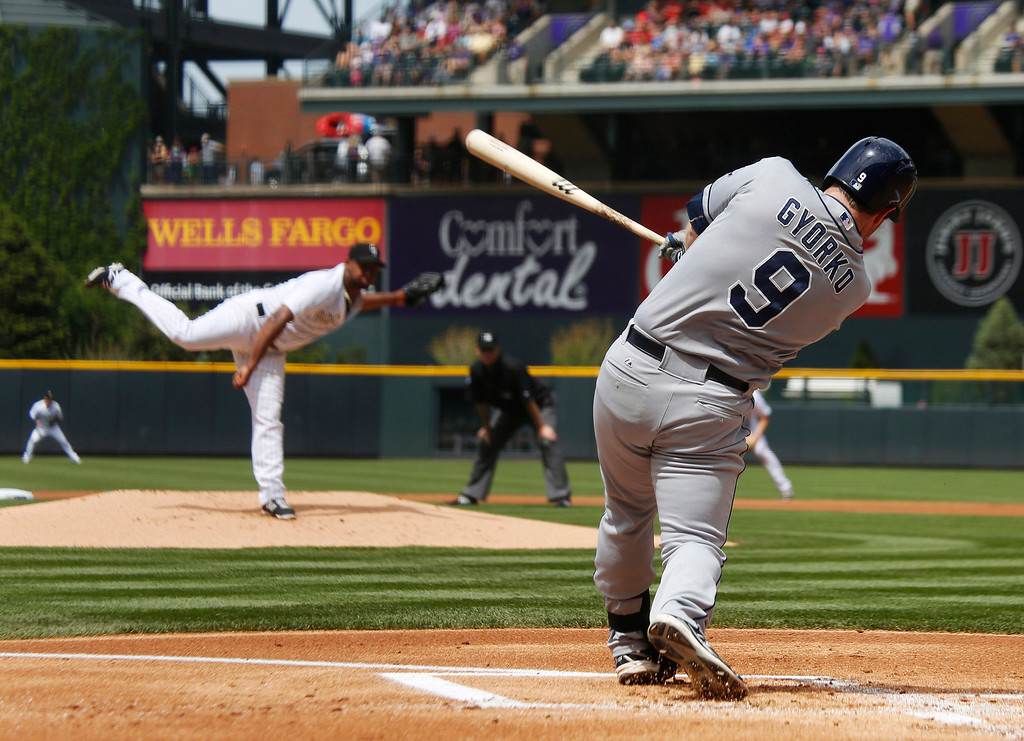 . San Diego Padres\' Jedd Gyorko, front, doubles against Colorado Rockies starting pitcher Juan Nicasio in the first inning of a baseball game in Denver on Sunday, May 18, 2014. (AP Photo/David Zalubowski)