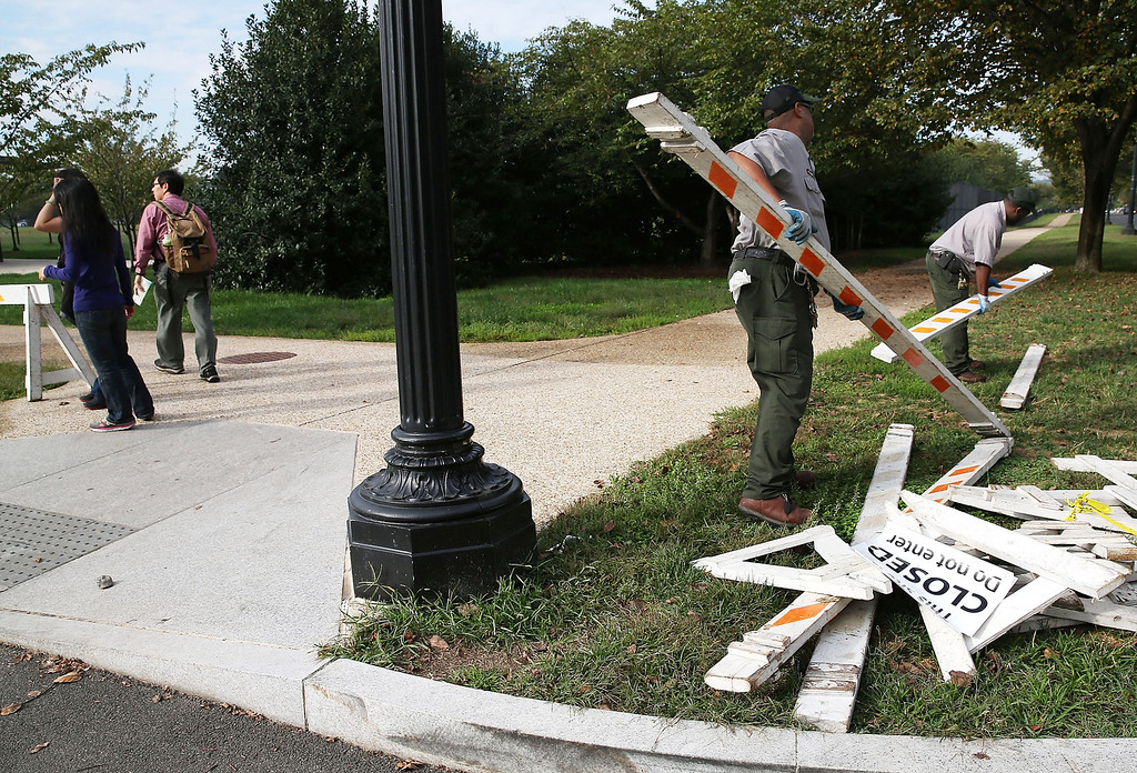 . Tourists walk past as U.S. Park Service workers remove barricades that was used to close the Martin Luther King Memorial on the morning after a bipartisan bill was passed by the House and the Senate to reopen the government and raise the debt limit, on October 17, 2013 in Washington, DC. President Obama signed the bill into law, that will fund the government until January 15, 2014 and allow the government to pay bills until February 7, 2014.  (Photo by Mark Wilson/Getty Images)