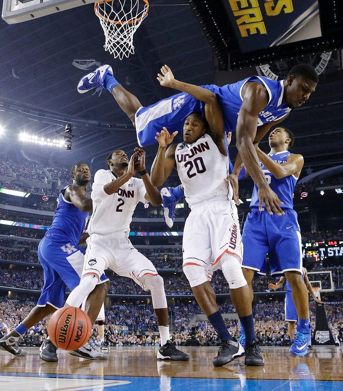 . Kentucky forward Alex Poythress (22) goes over Connecticut guard Lasan Kromah (20) during the second half of the NCAA Final Four tournament college basketball championship game Monday, April 7, 2014, in Arlington, Texas. Connecticut won 60-54. (AP Photo/Eric Gay)
