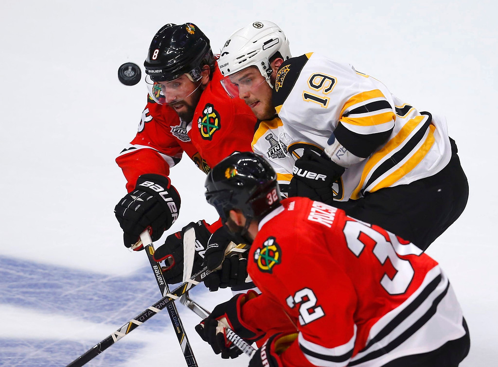 . Boston Bruins\' Tyler Seguin (19) battles for the puck with Chicago Blackhawks\' Nick Leddy (8) and Michal Rozsival (32) during the first period in Game 1 of their NHL Stanley Cup Finals hockey series in Chicago, Illinois, June 12, 2013. REUTERS/Jeff Haynes