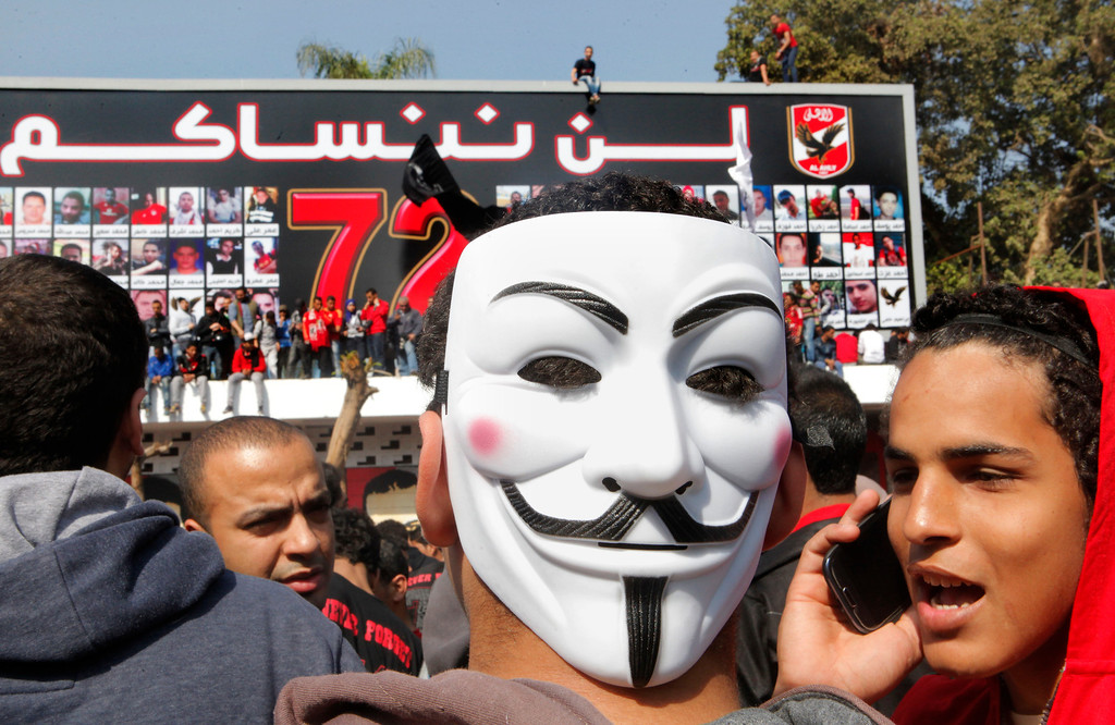 . An Egyptian soccer fan of the Al-Ahly club wearing a Guy Fawkes mask joins hundreds of fans in front of their club headquarters in Cairo, Egypt, Saturday, March 9, 2013.  (AP Photo/Amr Nabil)