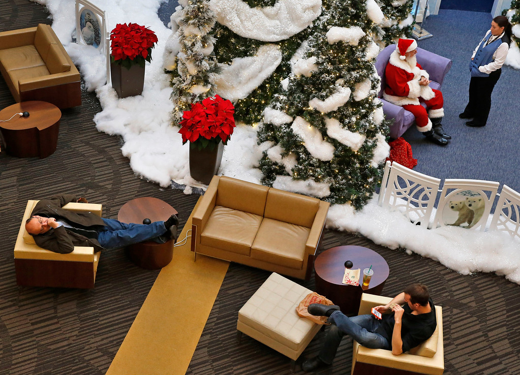 . A shopper sleeps, left, as Santa talks with his assistant, at the Ice Palace inside Cherry Creek Mall, in Denver, early Friday, Nov. 29, 213. Black Friday, the day after Thanksgiving, is the nation\'s biggest shopping day of the year. (AP Photo/Brennan Linsley)