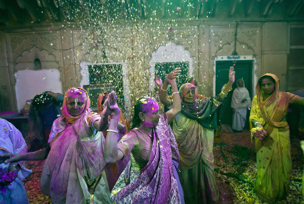 . Indian widows sing and dance while playing Holi with gulal (colored powder), flowers and water  in Vrindavan on March 14, 2014. B  AFP PHOTO/Prakash SINGH/AFP/Getty Images