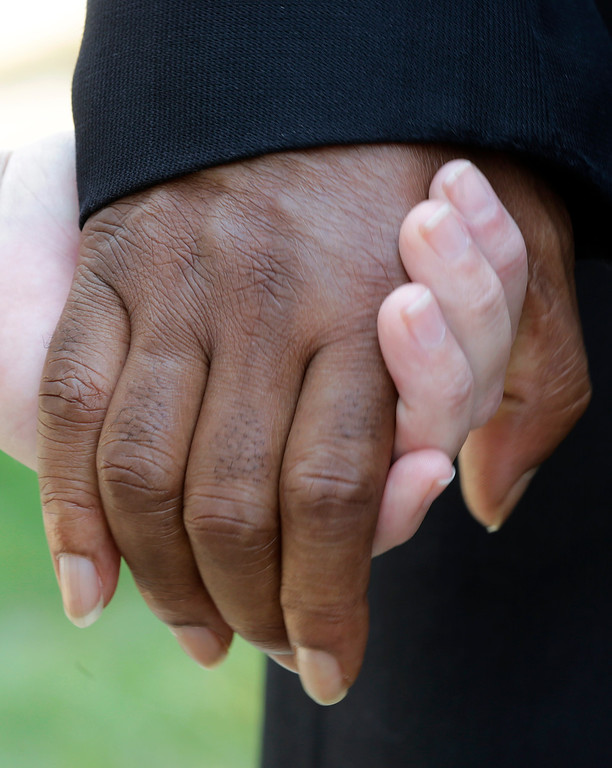 ". People of mixed races hold hands during a prayer outside the Dexter Ave. King Memorial Baptist Church in Montgomery, Ala., Wednesday, Aug. 28, 2013. Members were holding a bell ringing ceremony to honor the 50th anniversary of the ""I Had a Dream\"" speech by Rev. Martin Luther King Jr., who was pastor of the church in 1954. (AP Photo/Dave Martin)"