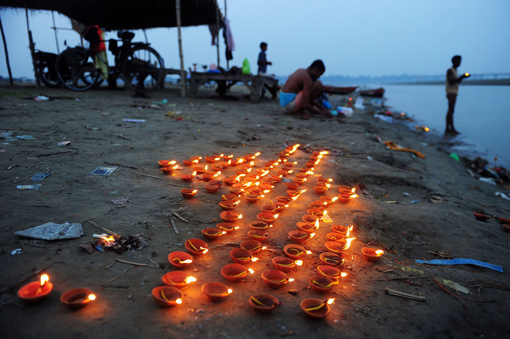 . Earthen lamps are lit at the Sangam at dusk during Diwali celebrations in Allahabad on November 3, 2013. Diwali marks the homecoming of the Hindu god Lord Ram after vanquishing the demon king Ravana and symbolizes taking people from darkness to light and the victory of good over evil. Sanjay Kanojia/AFP/Getty Images