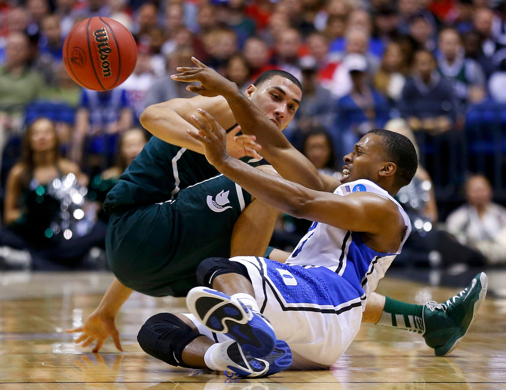 . Duke Blue Devils guard Tyler Thornton (3) passes after hitting the court against Michigan State Spartans guard Denzel Valentine (45) in the first half during their Midwest Regional NCAA men\'s basketball game in Indianapolis, Indiana, March 29, 2013.  REUTERS/Jeff Haynes