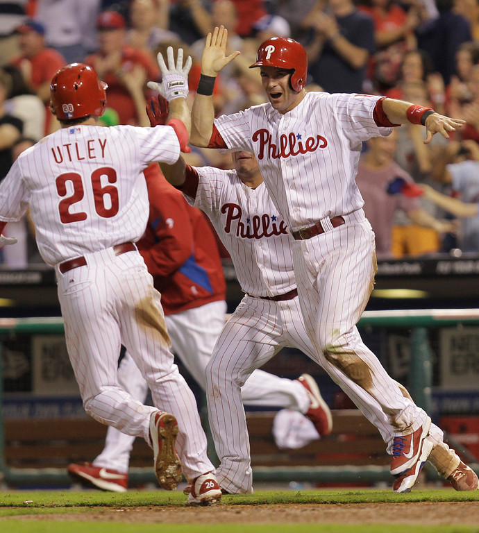 . Philadelphia Phillies\' Michael Young, right, is cheered by Chase Utley after making the game-winning run on a hit by Domonic Brown in the ninth inning of a baseball game to defeat the Colorado Rockies 5-4, Thursday, Aug. 22, 2013, in Philadelphia. (AP Photo/Laurence Kesterson)
