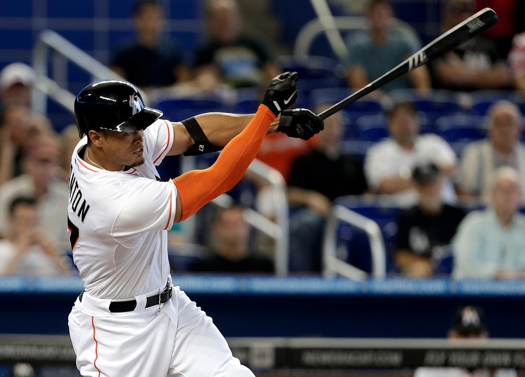 . Miami Marlins\' Giancarlo Stanton hits a double in the first inning of a baseball game against the Colorado Rockies, Thursday, April 3, 2014, in Miami. (AP Photo/Lynne Sladky)