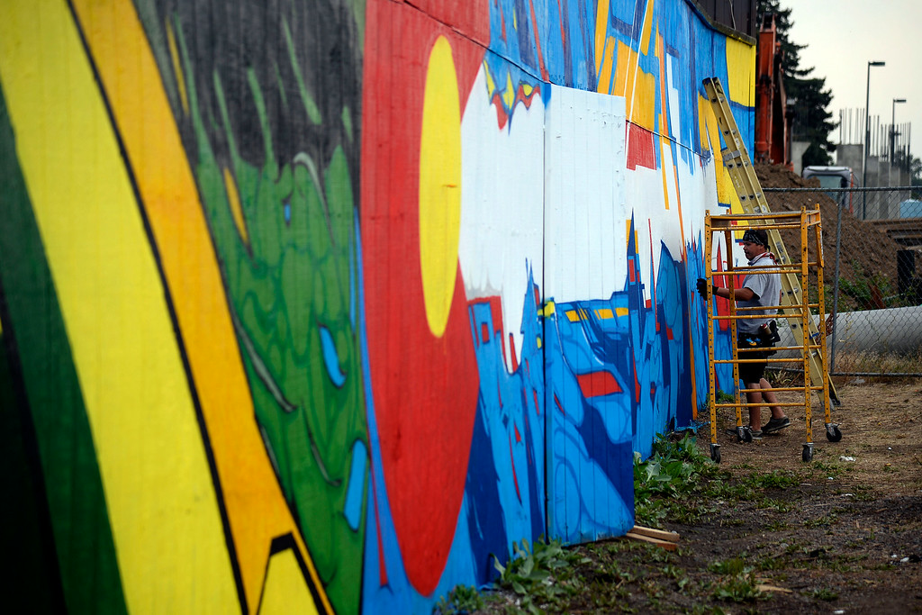 . Jon Lamb and Michael Ortiz (pictured) of Like Minded Productions work on a large mural outside of the Herbal Cure. The Mural that faces I-25 near the Washington St. and Emerson Street exit was photographed on Tuesday, July 15, 2014. (Photo by AAron Ontiveroz/The Denver Post)