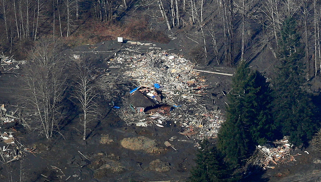 . A house destroyed by the massive mudslide that killed at least eight people and left dozens missing is shown in this aerial photo, Monday, March 24, 2014, near Arlington, Wash. The search for survivors grew Monday, raising fears that the death toll could climb far beyond the eight confirmed fatalities. (AP Photo/Ted S. Warren)