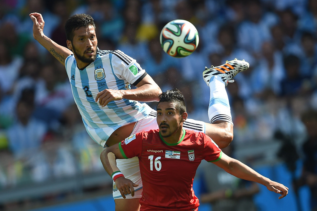 . Argentina\'s defender Ezequiel Garay (L) and Iran\'s forward Reza Ghoochannejhad vie for the ball during a Group F football match between Argentina and Iran at the Mineirao Stadium in Belo Horizonte during the 2014 FIFA World Cup in Brazil on June 21, 2014.  PEDRO UGARTE/AFP/Getty Images